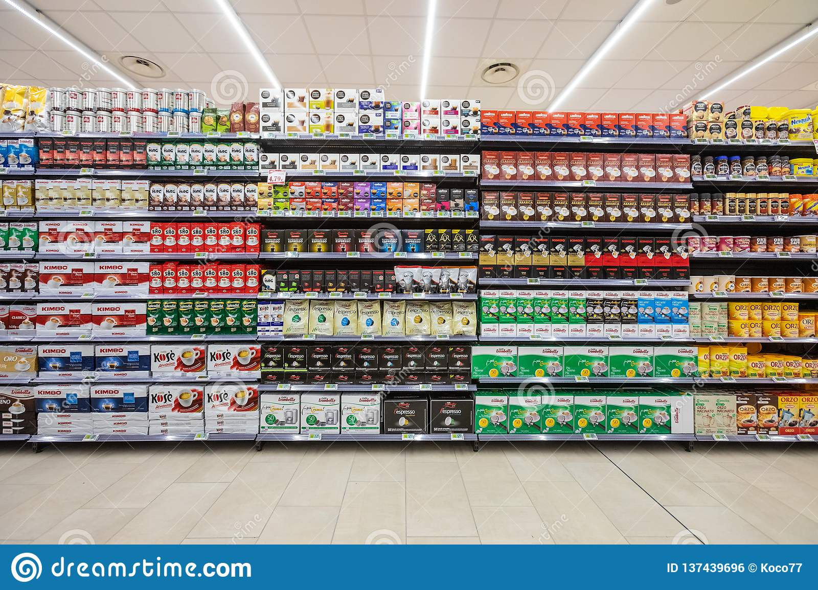 Several Packs Of Coffee On A Wall Of Shelves Front View