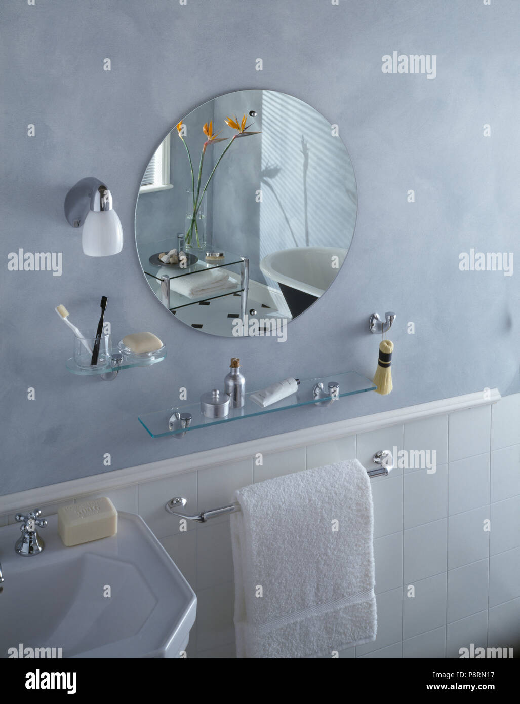 Circular Unframed Mirror And Glass Shelves Above White Towel