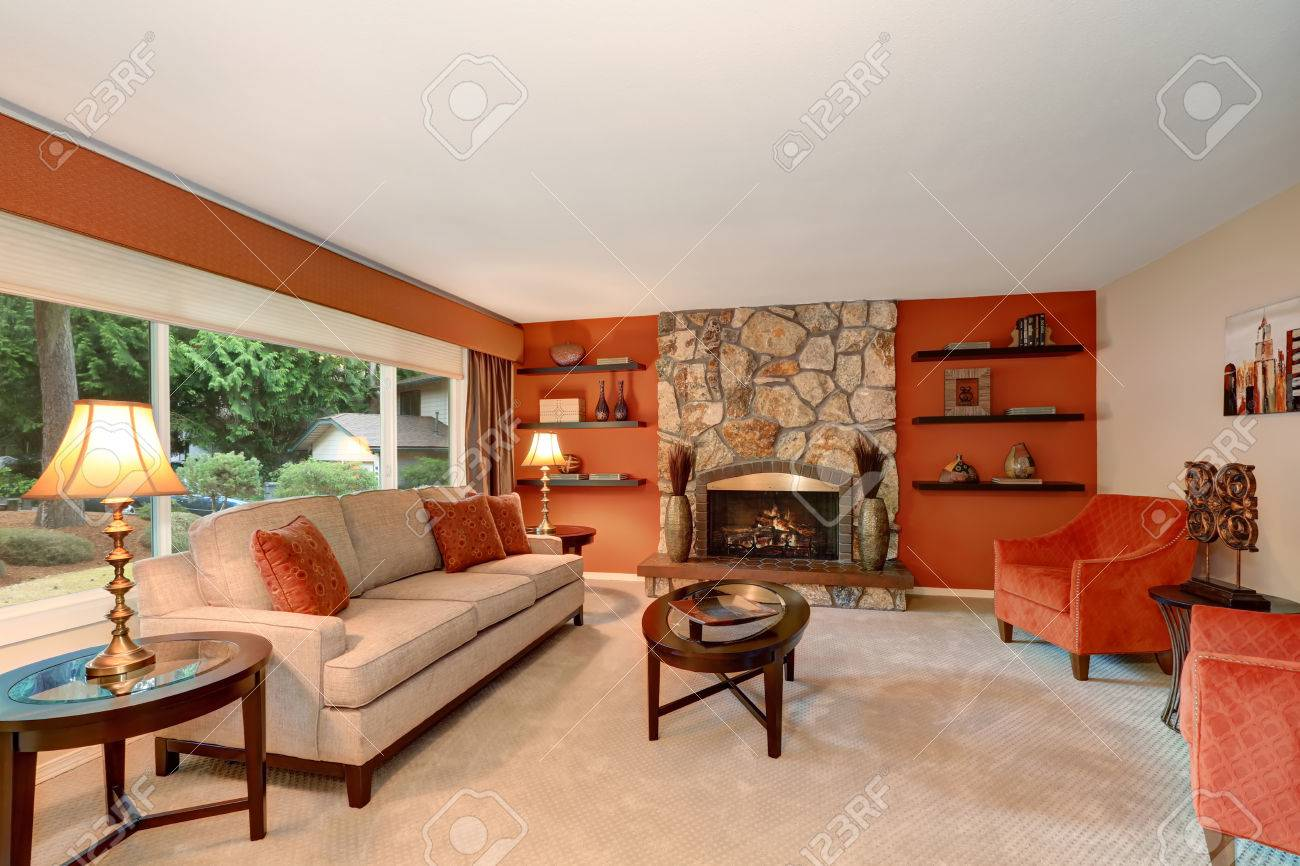 Cozy Family Room In Red Tones With Stone Fireplace And Some Shelves