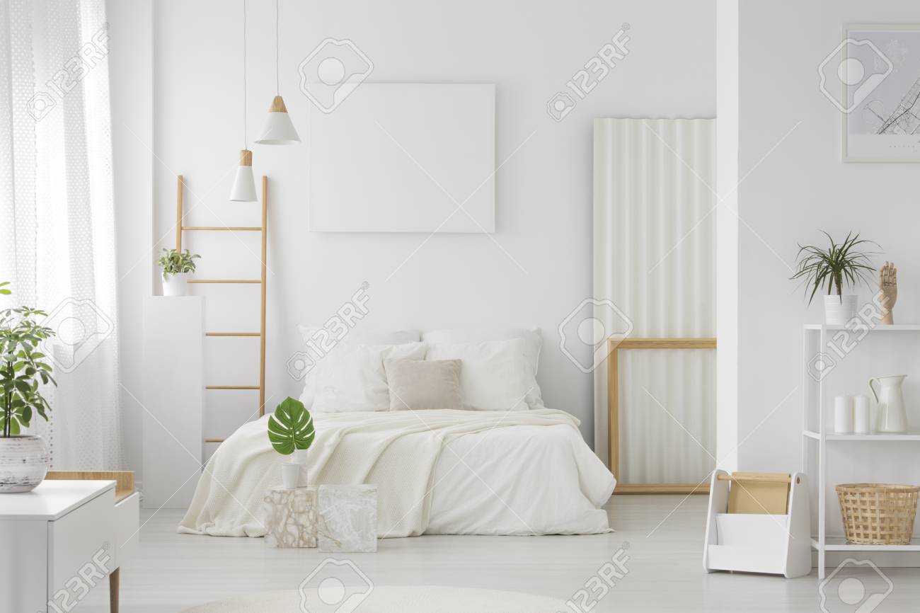 A White Bedroom With Large, King Size Bed, Shelves, Ladder And