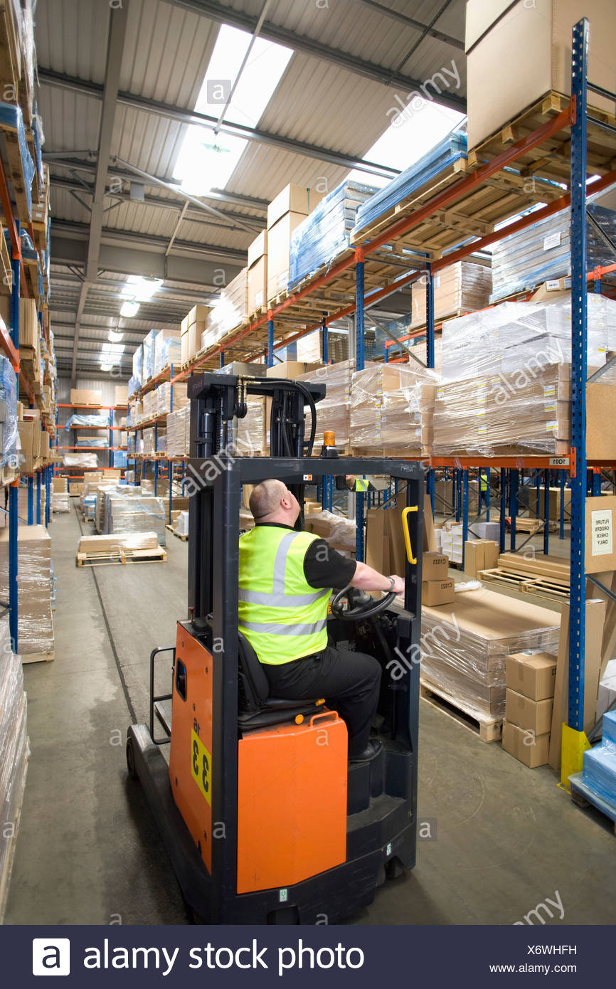 Warehouse Worker Operating Forklift And Looking Up At Shelves Stock