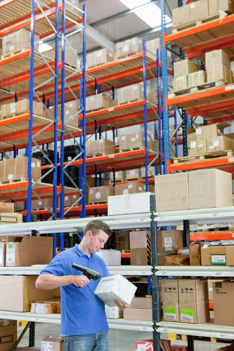 Worker Scanning Box Among Shelves In Distribution Warehouse Stock Photo