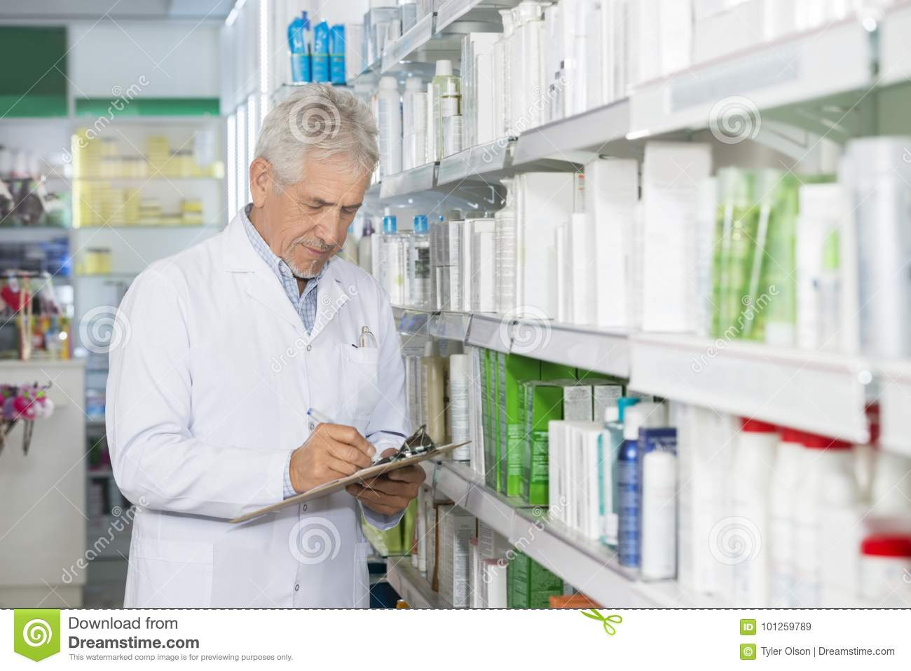 Chemist Writing On Clipboard While Standing By Shelves Stock Image