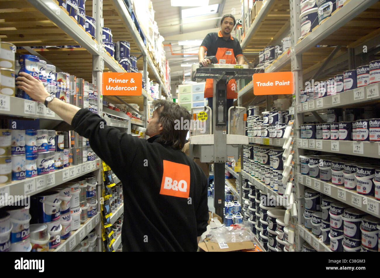 B&q Employees Restocking Shelves In A Paint Isle Stock Photo