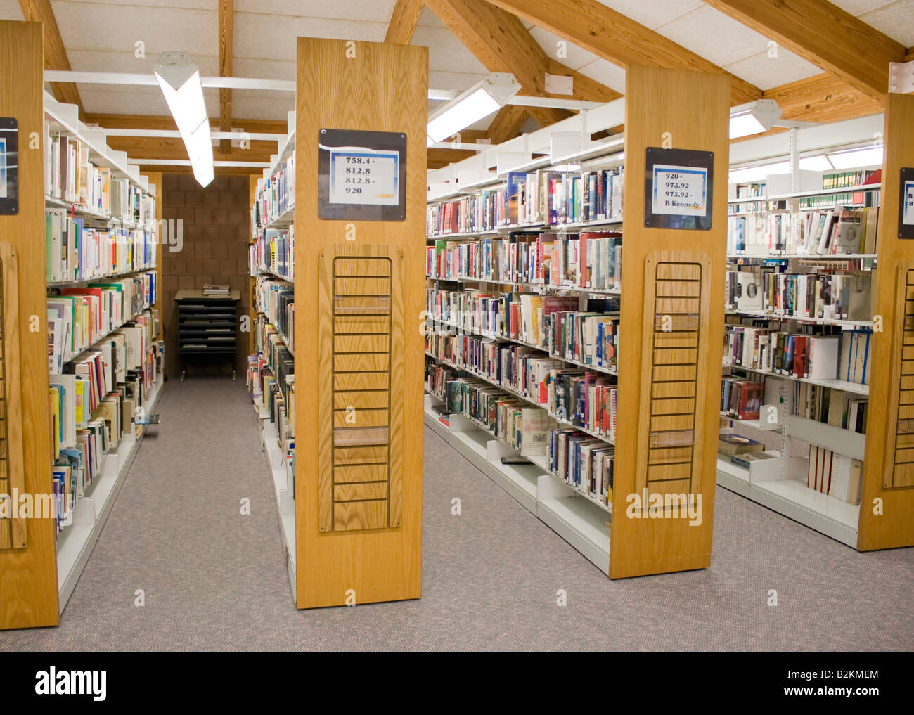 The Aisles In A Public Library With Shelves Full Of Books Stock