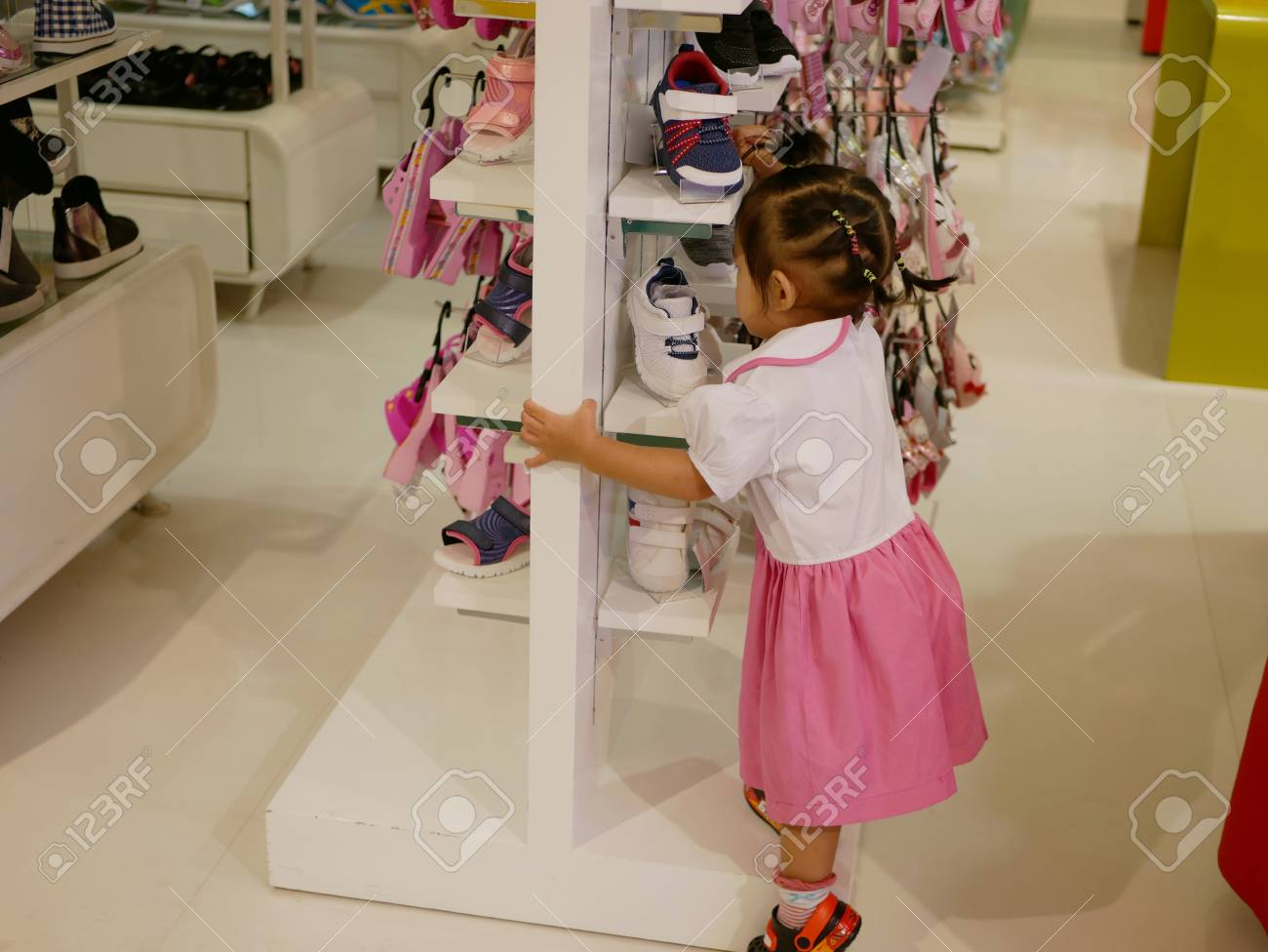 Little Asian Baby Girl, 19 Months Old, Trying To Climb Shoe Shelves