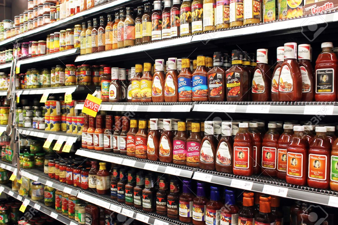 Variety Of Sauces And Tomato Ketchup Bottles On Shelves In A