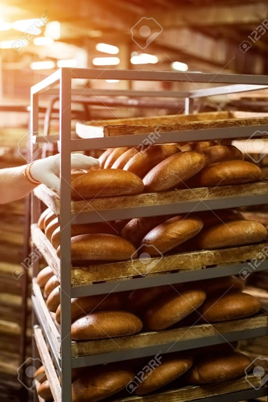 Brown Bread Loaves On Rack Hand Touching Bread On Shelves Big