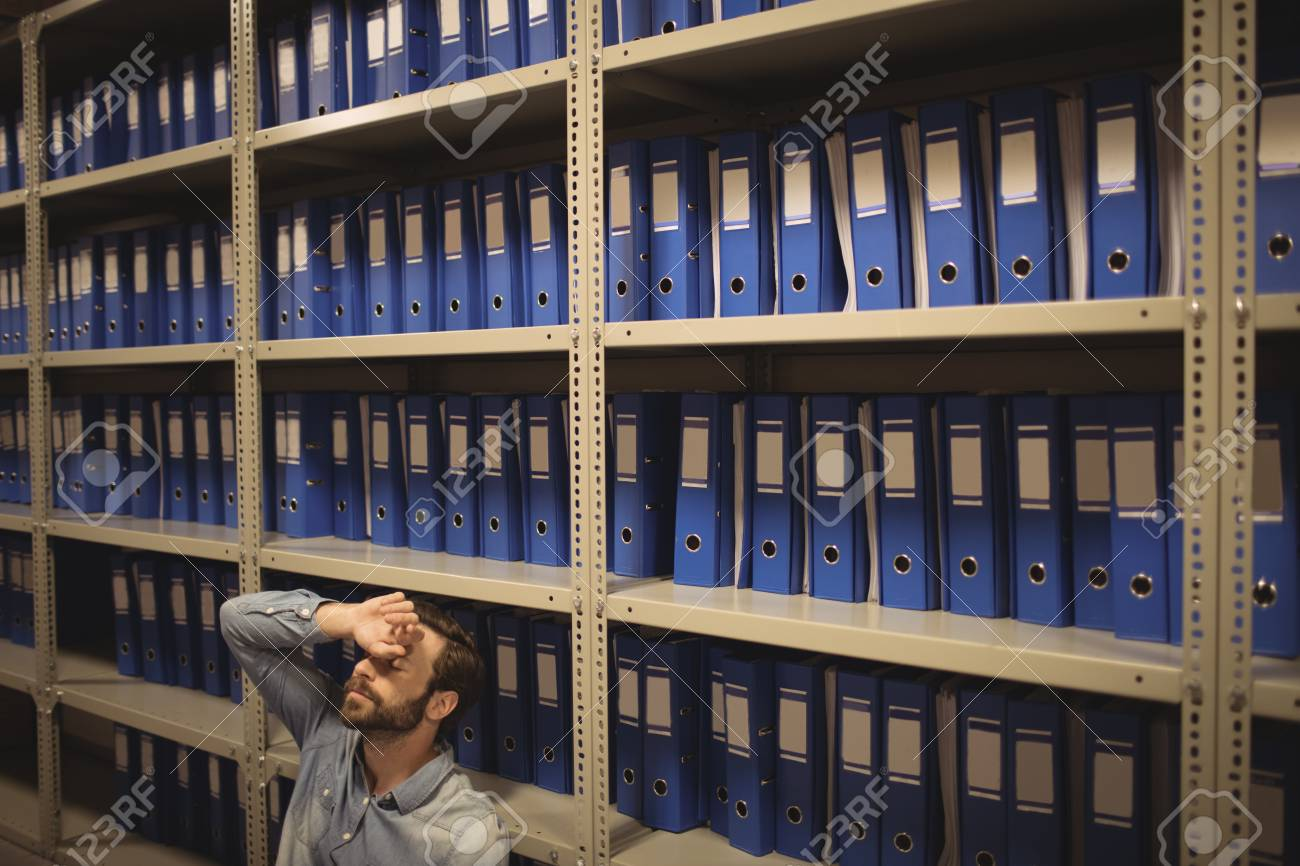 Tired Businessman Sitting By Shelves In File Storage Room