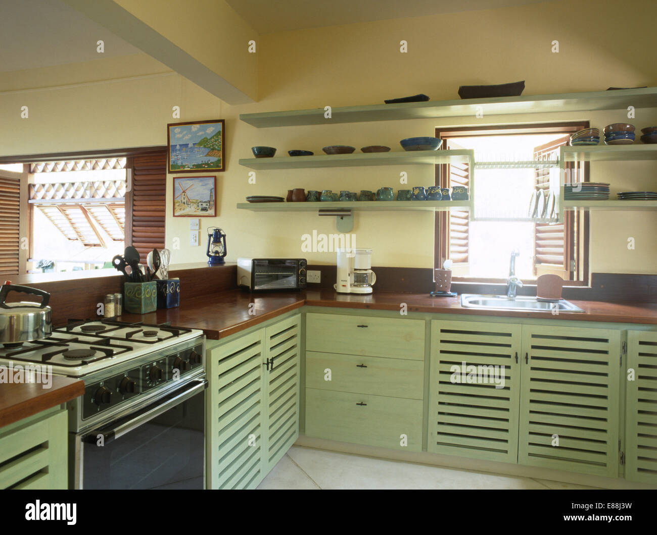 Shelves Above Pastel Green Units With Wood Worktops In