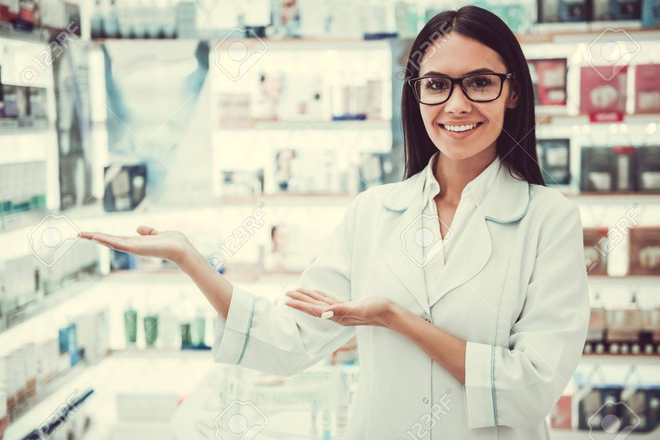 Beautiful Female Pharmacist Is Showing Shelves With Medicine,