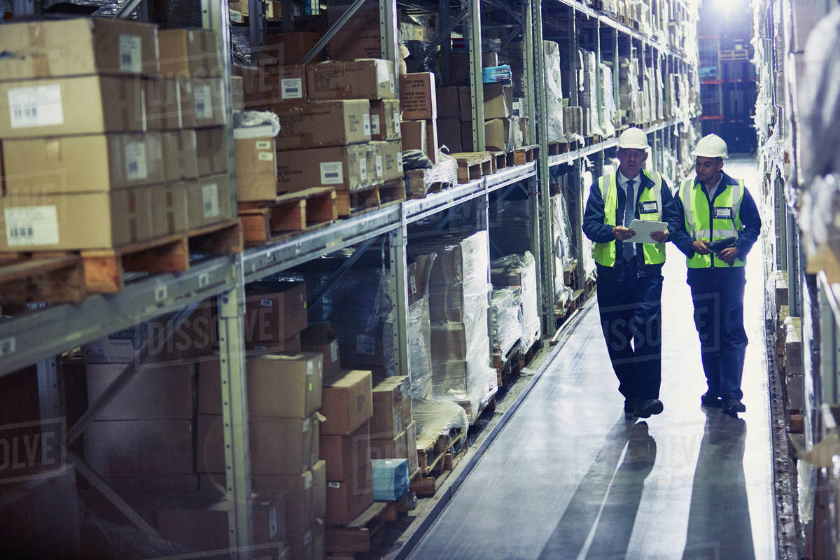 Manager And Worker With Clipboard Walking Along Merchandise On Shelves In  Distribution Warehouse Stock Photo