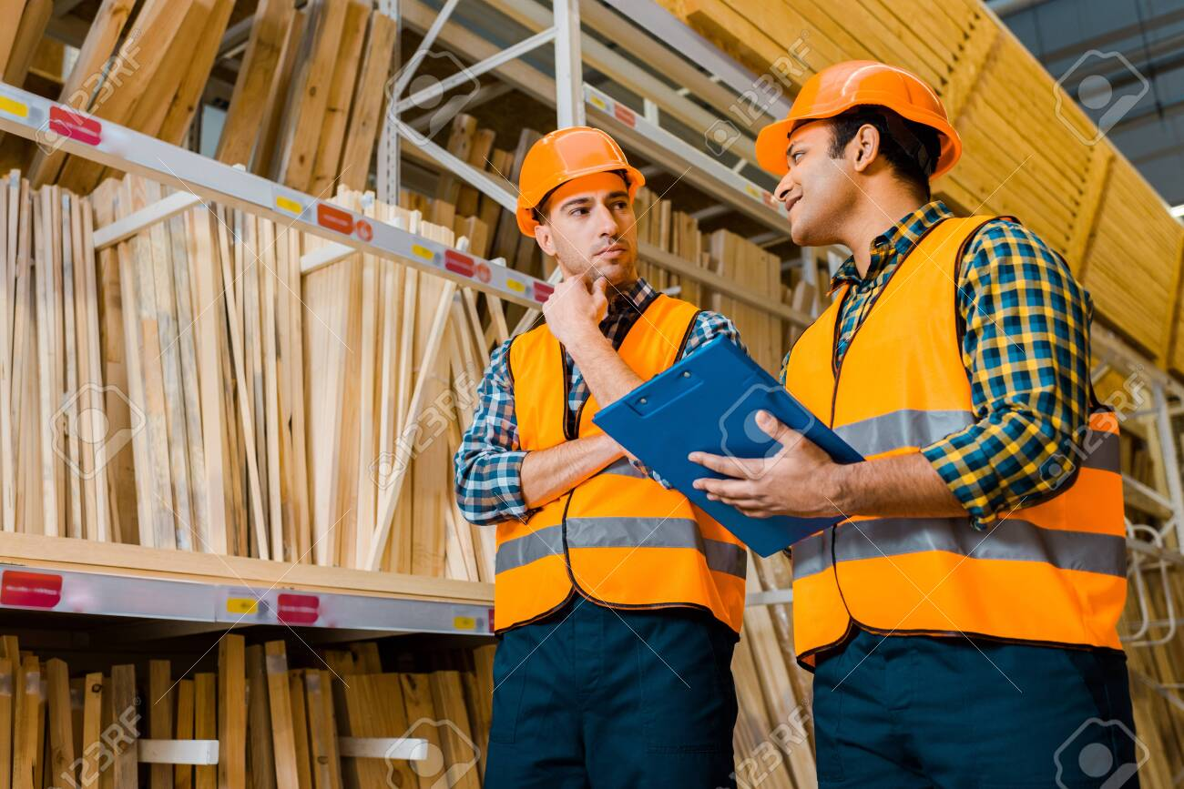 Thoughtful Multicultural Workers Standing Near Shelves With Wooden