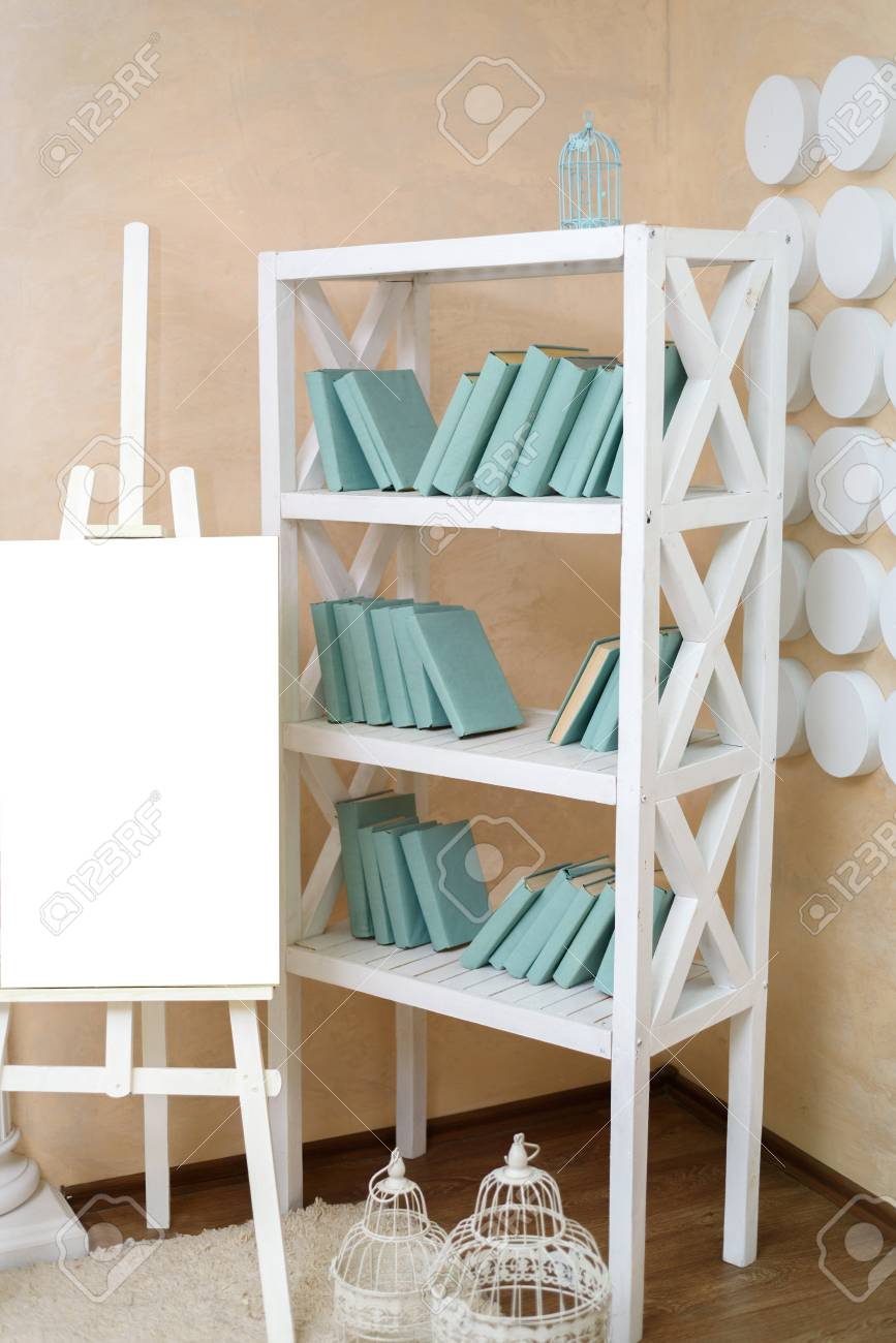 Books On The Shelves Easel With Blank Sheet Of White Paper Next