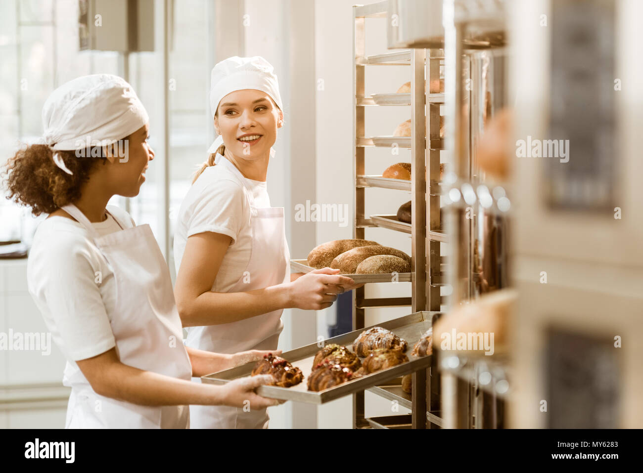 Attractive Female Bakers Putting Fresh Pastry On Shelves At