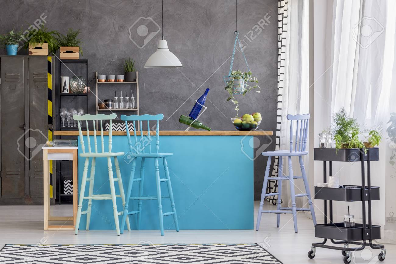 Black Shelves Near Blue Kitchen Island And Bar Stools In Room