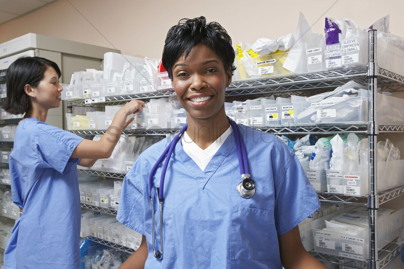 Portrait Of Female Doctor Nurse Standing By Shelves With